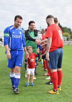 Captain Gary Knowelden leads the mascot through the handshakes