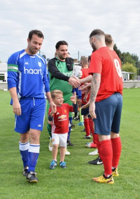 Captain Gary Knowelden leads the mascot through the handshakes