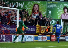 Tyler Harvey runs off to celebrate in front of the away fans...