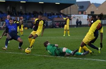 Karl Oliyide pokes past Rhys Forster